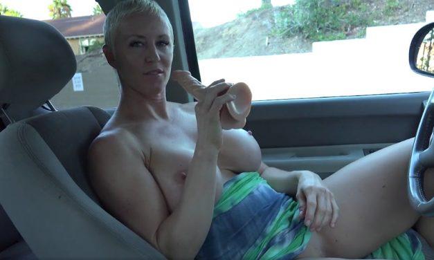 Hete milf, blond, kort haar en grote tieten, is in de auto aan het masturberen