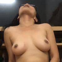 Aziatische milf met geil brilletje op is in de huiskamer aan het masturberen